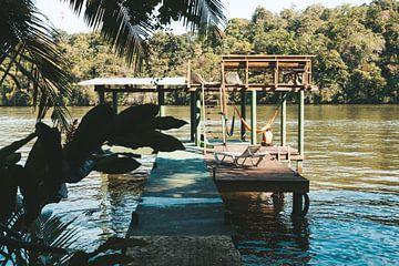 Houten aanlegsteiger op de Rio Dulce voor het Round House Hostel in Guetamala van Michiel Dros
