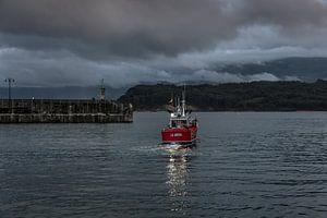 Kleine vissersboot verlaat de haven vlak voor donker