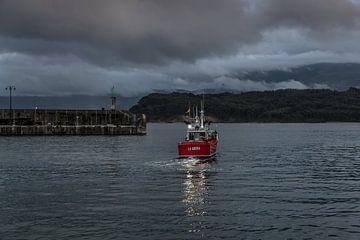 Un petit bateau de pêche quitte le port juste avant la tombée de la nuit sur Harrie Muis