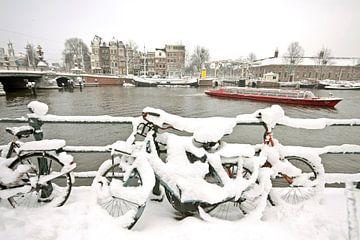 Besneeuwde fietsen aan de rivier de Amstel in Amsterdam van Nisangha Masselink