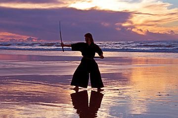 Jonge  samurai vrouw met japans zwaard Katana) bij zonsondergang op het strand van Nisangha Masselink