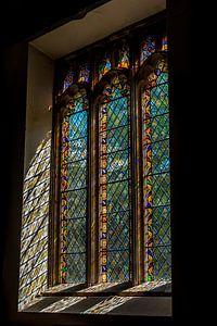 Glas in lood raam in oud kerkje in een klein dorpje in Devon, Engeland