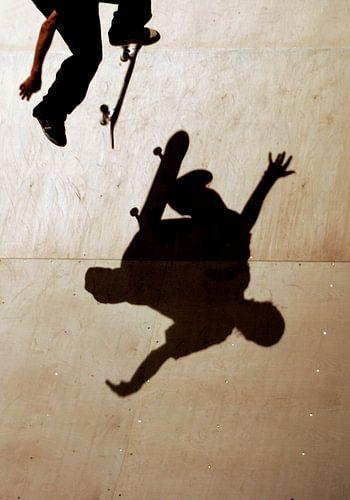 Een skateboarder springt over zijn schaduw