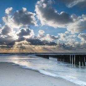 Zonnestralen achter de wolken op strand Zoutelande van Bas Verschoor