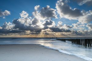 Zonnestralen achter de wolken op strand Zoutelande