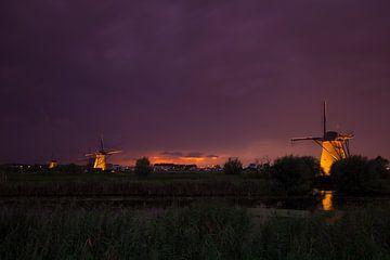 Verlichte Windmolens in Kinderdijk na zonsondergang van