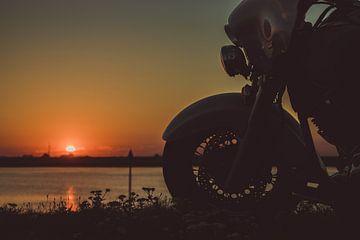 rustende motorrijder kijkt naar de zonsondergang van Eddie Anthonisse