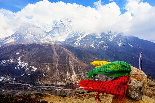 Prayer flags blowing in the wind, high on a Himalayan peak. van Joris de Bont