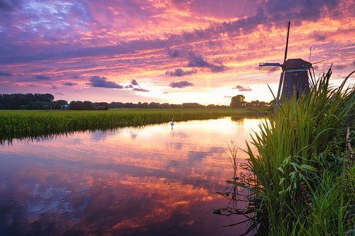 Zonsondergang in een landschap met molen en sloot