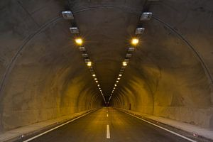 Eindeloze tunnel met autoweg en verlichting