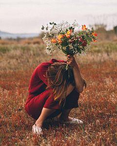 Meisje gehurkt met bloemen van Colette der Kinderen