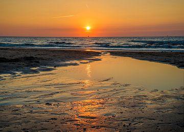 Reflectie van ondergaande zon op het strand van Fred Leeflang