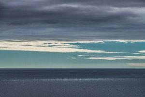 Lichtvlek op de oceaan door spleet in t wolkendek