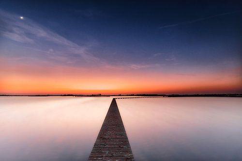 Houten voetpad bij zonsondergang van
