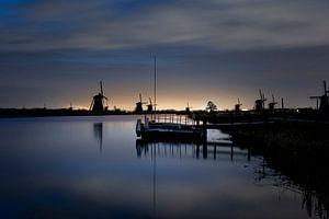 Historische Nederlandse windmolens langs een breed kanaal in Kinderdijk van Tjeerd Kruse