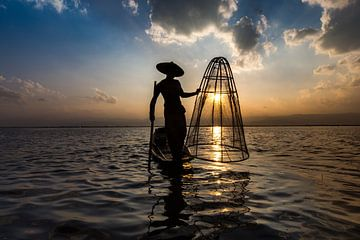 Visser die met traditionele boot op het Inle meer in Myanmar op ouderwetse wijze met een vis korf vi van Wout Kok