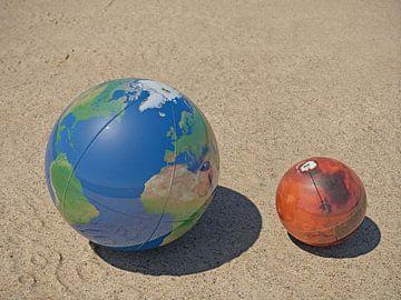 De Aarde en Mars op het strand