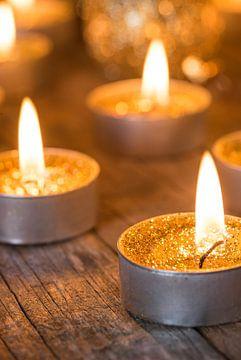 Glimmende adventskaarsen voor de kersttijd met gouden glitter kerstballen versieringen van Alex Winter