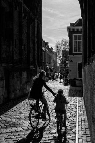Moeder en kind fietsen onder de Dom van