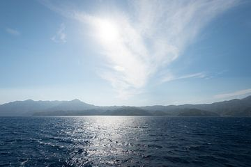 Wolk en zon boven zee