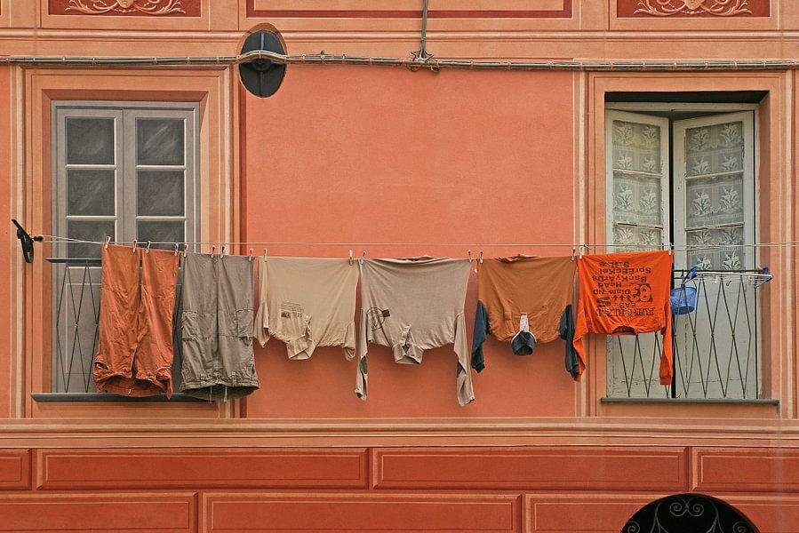 Monochrome uitstalling van wasgoed voor zelfde kleur gevel.