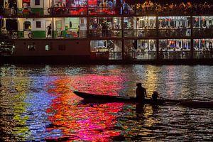 Vissersbootje in het licht van een partyboot