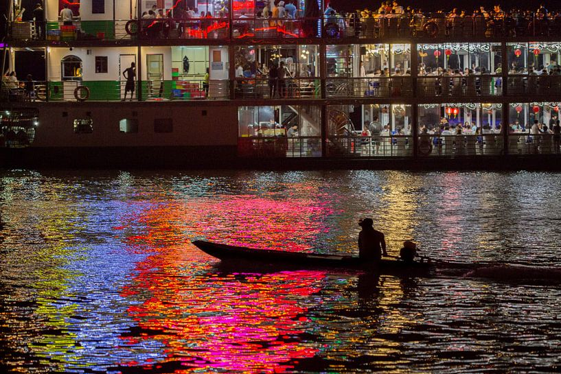 Vissersbootje in het licht van een partyboot van Fleur Halkema