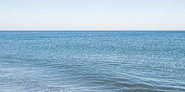Noordzee golf in een kalme zee met een golfbreker markerings paal. van MICHEL WETTSTEIN