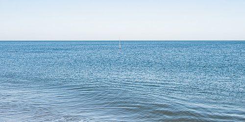 Noordzee golf in een kalme zee met een golfbreker markerings paal.