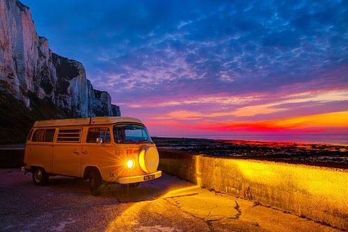Hippiebusje Volkswagen T2 tijdens krachtige zonsondergang in Normandië, Frankrijk bij het strand met