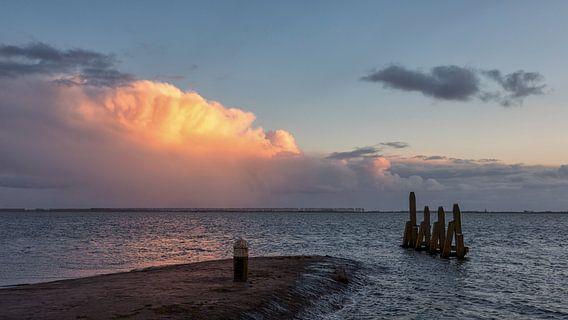 Verlichte wolk boven water van Bram van Broekhoven