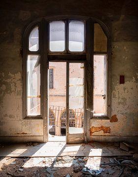 Fenster in verlassenem Gebäude mit Sonnenlicht.