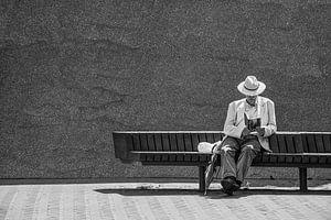 Man leest boek op bankje.