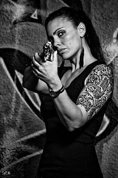 Getatoeëerde vrouw met een pistool in zwart wit
