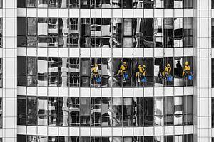 Glazenwassers in geel tegen monochroom flatgebouw