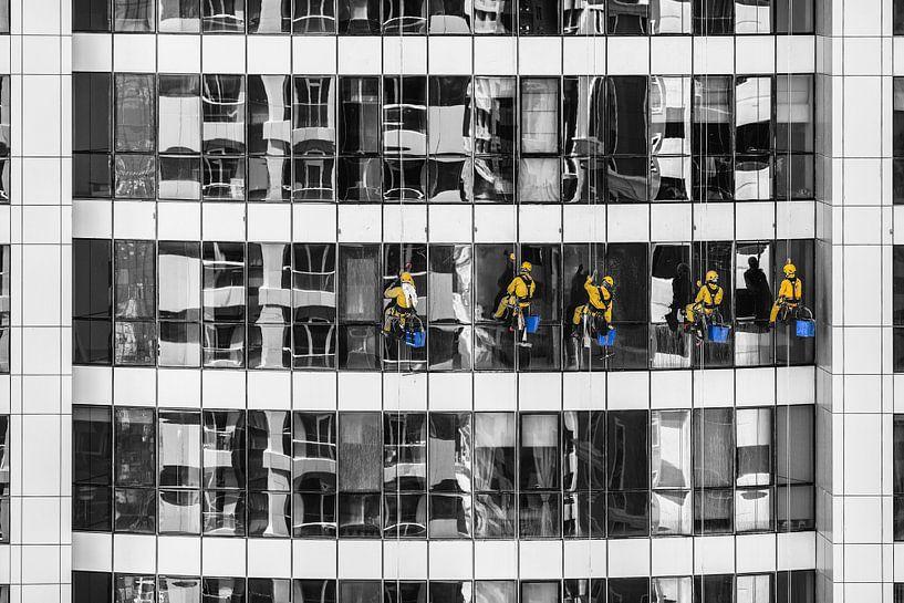 Glazenwassers in geel tegen monochroom flatgebouw van Atelier Liesjes
