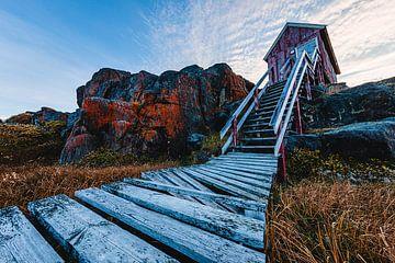 Charakteristisches Holzhaus mit Treppe an der grönländischen Felsenküste von Martijn Smeets