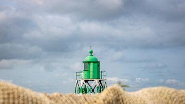Het groene lichtbaken van Stavoren met op de voorgrond een detail van een visnet. van Henk Van Nunen Fotografie