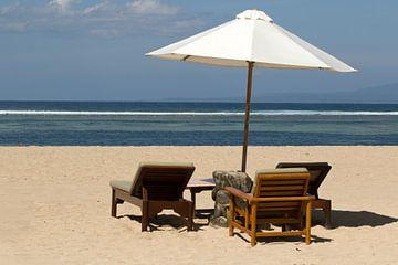 Parasol met ligstoelen op het strand van Sanur op Bali van Maurice de vries