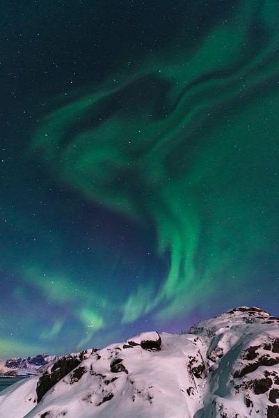 Noorderlicht of Aurora Borealis over de besneeuwde bergen in de winter van Sjoerd van der Wal