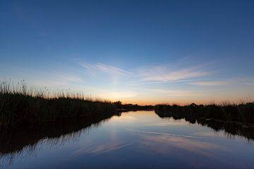 Spiegeling van lucht en riet tijdens zonsondergang van Marieke_van_Tienhoven