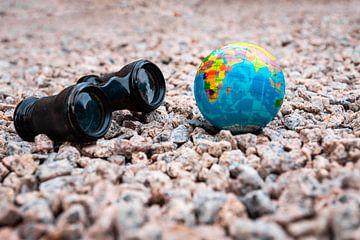 Verrekijker met een kleine aarde op kiezelstenen in de zomer van Denny Gruner