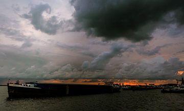 Vrachtschip met dreigende lucht en oranje gloed op het Markermeer van Anneriek de Jong