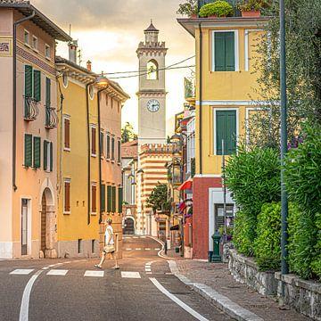 Italië, Gardameer, Castelletto | Vrouw steekt over in typisch Italiaans dorp van Hessel de Jong