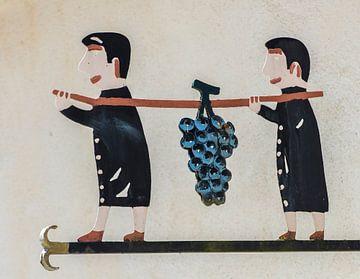 Twee mannen dragen druiventros van Daan Kloeg