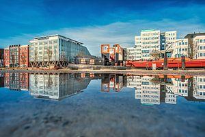 De Sneker trekweg in Leeuwarden weerspiegeld in een plas