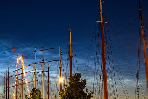 Schepen afgemeerd aan de IJssel in Kampen met lichtende nacht wolken