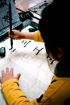 Chinees meisje leert karakters schrijven von André van Bel