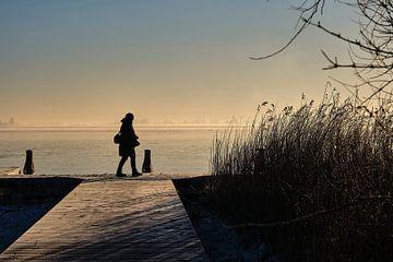 Eenzaam wandelende  fotograaf langs het bevroren meer bij zonsopkomst in koude winter van BJ Fleers