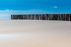 Houten paaltjes op het strand van